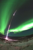 Een raketlancering met op de achtergrond aurora, noorderlicht