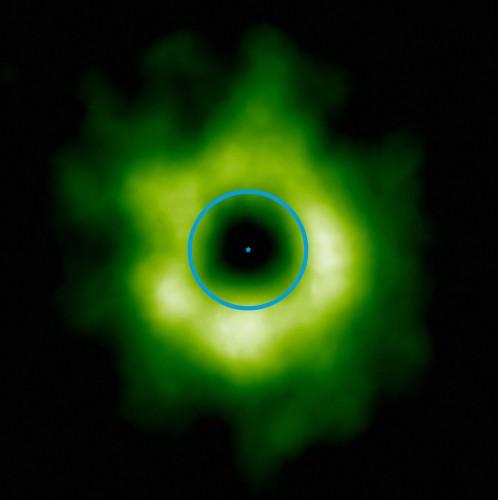 Deze opname, gemaakt door de ALMA-sterrenwacht in Chili, toont het (groen ingekleurde) gebied rond de ster TW Hydrae (aangeduid met een stip) waar zich koolstofmonoxide-sneeuw heeft gevormd. De blauwe cirkel geeft aan waar de baan van Neptunus ligt als we dit stelsel afbeelden op de schaal van ons eigen zonnestelsel. De overgang naar koolmonoxide-sneeuw kan ook de binnenste begrenzing aangeven van het gebied waar zich kleinere, ijsachtige objecten vormen, zoals kometen en dwergplaneten als Pluto en Eris.