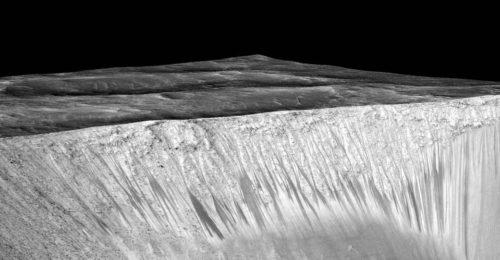 Donkere strepen, de zogenaamde reccurring slope lineae, aan de wand van de Garni-krater op Mars.