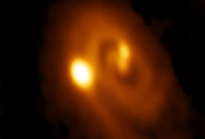 ALMA-opname op een golflengte van 1,3 mm van de drievoudige protoster L1448 IRS3B. De opname laat de spiraalstructuur en de emissie naar de drie protosterren zien. De helderste emissie is richting het buitenste en jongste lid van het trio. De opname beslaat 3,5 boogseconden, wat overeenkomt met circa 800 astronomische eenheden oftewel achtmaal de grootte van ons zonnestelsel.