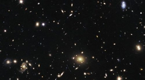 "The heart of a vast cluster of galaxies called MACSJ1720+35 is shown in this image, taken in visible and near-infrared light by the NASA/ESA Hubble Space Telescope. The galaxy cluster is so massive that its gravity distorts, brightens, and magnifies light from more distant objects behind it, an effect called gravitational lensing. In the top right an exploding star nicknamed Caracalla and located behind the cluster can just be made out. The supernova is a member of a special class of exploding star called Type Ia, prized by astronomers because it provides a consistent level of peak brightness that makes it reliable for making distance estimates. Finding a gravitationally lensed Type Ia supernova gives astronomers a unique opportunity to check the optical ""prescription"" of the foreground lensing cluster. The supernova is one of three exploding stars discovered in the Cluster Lensing And Supernova survey with Hubble (CLASH), and was followed up as part of a Supernova Cosmology Project HST program. CLASH is a Hubble census that probed the distribution of dark matter in 25 galaxy clusters. Dark matter cannot be seen directly but is believed to make up most of the universe's matter. The image of the galaxy cluster was taken between March and July 2012 by Hubble's Wide Field Camera 3 and Advanced Camera for Surveys."